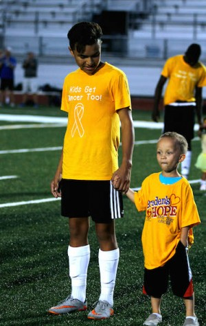 Oscar Aguliar Jr. holds hands with a kid that has survived cancer
