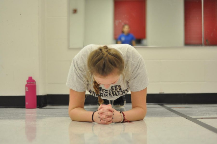 Fingers crossed and head down, sophomore Adie Basey does a 30 second plank. photo by Rilee Morrow