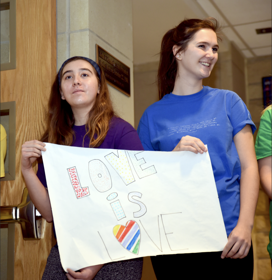 Greeting classmates as they walk in, SM East students Ellie Van Gordon and Libby O'Connor hold messages of support and unity on the day of the WBC protest. photo by Elise Baker