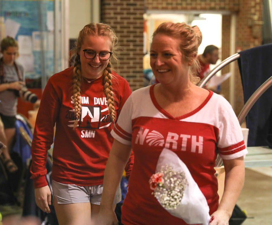 Smiling%2C+senior+swim+manager+Allie+Kempfer+walks+alongside+her+mom+as+her+name+gets+called+during+senior+night.