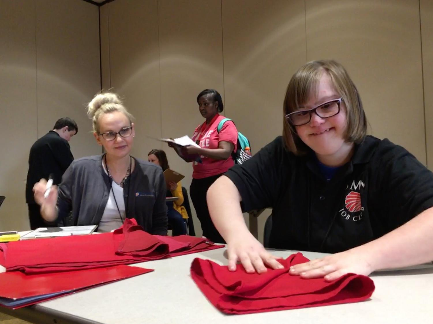Senior Katie Saesnick participates in the napkin folding competition at the annual Job Olympics event March 28.