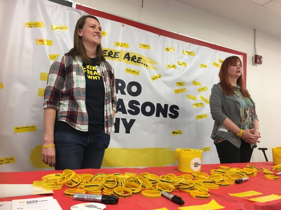 """Smiling at students approaching the table, Zero Reasons Why representative Cindy Knudsen helps hold a banner-signing event at North during lunch April 3. """"It's been encouraging to see how many teens really care about this message,"""