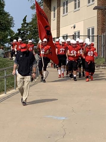 Coach Walter leads the football team to their first game of the season.