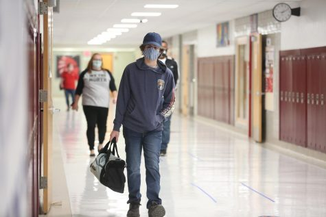 Junior Cole McNickle walks to one of his classes. To reduce transmission rates and overall population, student
