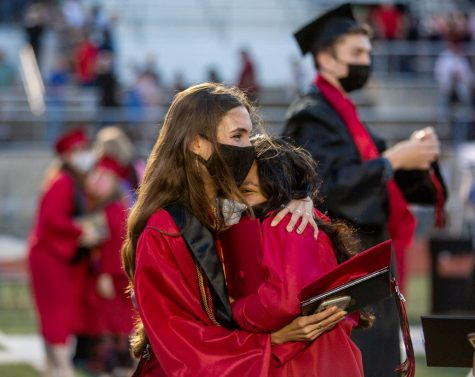 Graduates Emma Bell and Elizeth Moncada embracing after the ceremony.